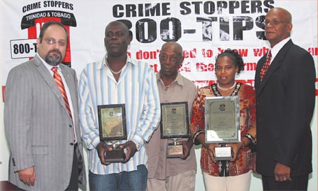Mr. John Aboud, chairman of Crime Stoppers T&T (far L) and Mr. Junia Regrello, Parliamentary Secretary, Ministry of Community Development, Culture and Gender Affairs (far R) present the awards to (L to R) Mr. Prior Superville of Friends of the Sangre Grande Civic Centre, Mr. Augustus Mark of Casablanca Pan Yard, Belmont and Ms. Cheryl Joseph of Believers' Training Centre, Sixth Company Village, Princes Town. Also in attendance was the Minister of National Security, Senator Martin Joseph.